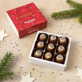 a small box of 9 fizzy Christmas pudding chocolates by Chococo with popping candy on top and stars scattered around the chocolate box