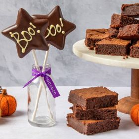 Chococo plain dark chocolate brownie on marble top with star boo lolly in a milk glass with felt pumpkins around for Halloween