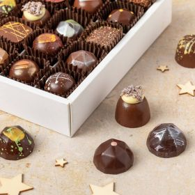 a box of 16 handcrafted luxury festive Christmas chocolates in their box with Xmas trees and pine cones around it