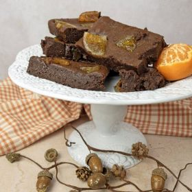 Chocolate orange brownie by Chococo on a white cake stand surrounded by orange gingham napkin and acorn garland.