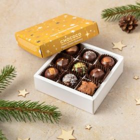 a small box of 9 handcrafted vegan dark handcrafted festive chocolates by Chococo with yellow gold star lid with wooden stars scattered around