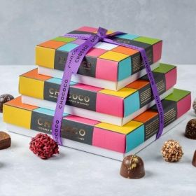 A stacked cascade of Chococo chocolate boxes with fresh milk chocolates around.