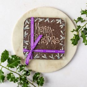 giant dark chocolate bar with hand pipped Merry Christmas message. hand decorated with holly design and surrounded by holly, on a marble plate and linen napkin