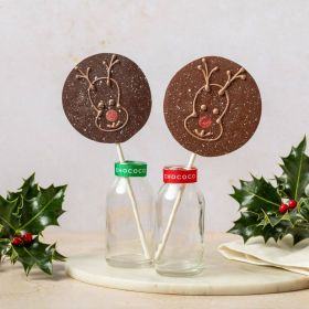 hand piped milk chocolate lolly by Chococo with reindeer face. titled in a small glass milk jar surround with real holly and linen napkin