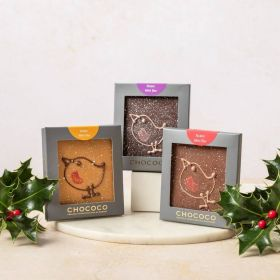 Dark chocolate mini bar by Chococo with hand-piped robin design on. Packaged in a grey box sat next to fresh real holly with red berries on