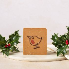 gold chocolate mini bar by Chococo with hand-piped robin design on. Packaged in a grey box sat next to fresh real holly with red berries on