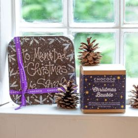 a personliased dark chocolate message bar by chococo on the window sill with Christmas baubles and fern cones