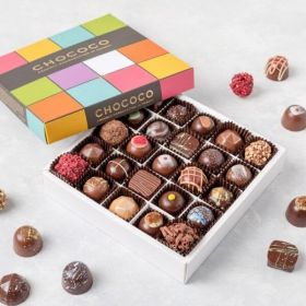 A box of fresh chocolates by Chococo using fresh ingredients with cherries, raspberries, buttons, caramel & honeycombe around