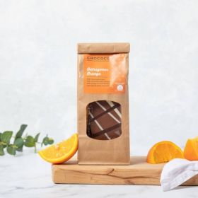 Milk Chocolate Outrageous Orange Slabs by Chococo on chopping board with Fresh Orange wedges and linen napkin