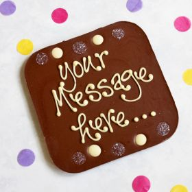 A Chococo giant milk chocolate bar where you can write a personalised message on surrounded by buttons. proudly handcrafted in Dorset