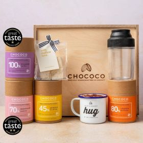 a close up of the inside of the deluxe hot chocolate hamper with hot-chocolate tubs, marshmallows, shaker, and enamel mug