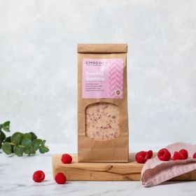 White Chocolate Ravishing Raspberry Slabs by Chococo on a chopping board with pale pink linen napkin and fresh raspberries.