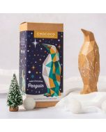 Gold chocolate geometric penguin by Chococo looking up to a north star silver Christmas decoration in a snowy forest with Christmas trees around
