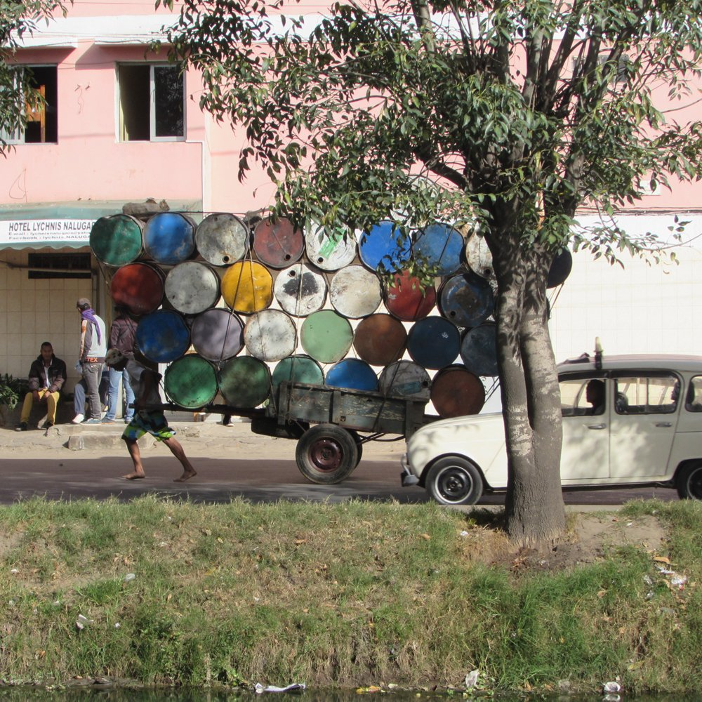 man pulling cart stacked with oil drums madagascar